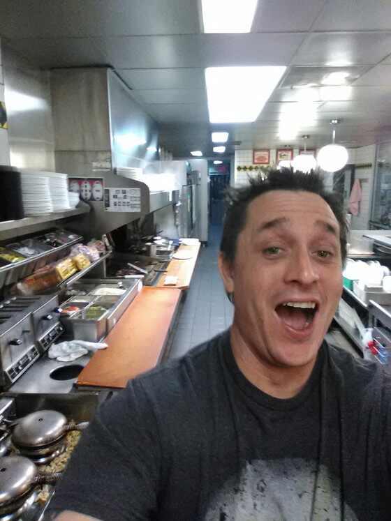 Homem cozinha próprio lanche em restaurante