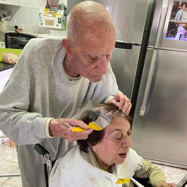 Elderly husband colors wife's hair so she feel well groomed