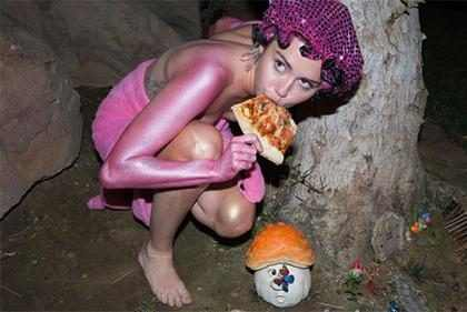 Miley Cyrus come pizza seminua em jardim