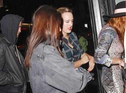 Robert Pattinson assiste show com três garotas